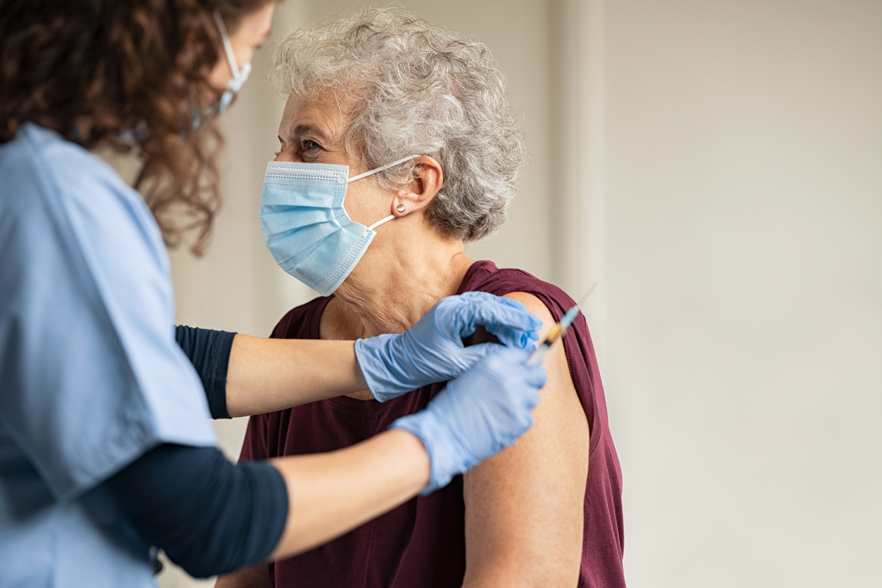Elderly lady receiving COVID-19 vaccine.