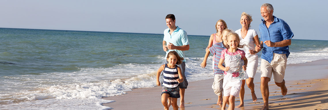 Large caucasian family running on the beach, happy.